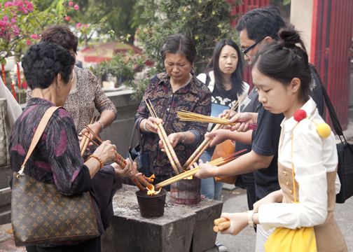Visitors lighting incense inside the frint gate of A-Ma Temple, Macau