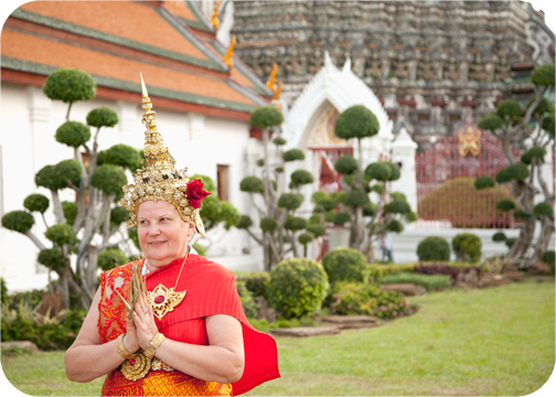 A woman in traditional costume outside Wat Arun: Bangkok, Thailand