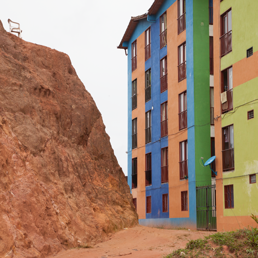 Block of colorful apartments next to a red rock: Guatape, Colombia
