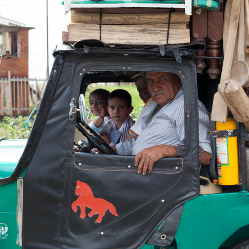 Yipao-Parade-Jeeps piled high with furniture. The driver-and- his family: Armenia, Colombia