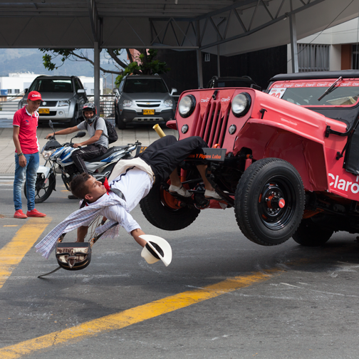 Yipao-Parade-Willys Jeep in the acrobatic group and driver hanging off the front bumper: Armenia, Colombia