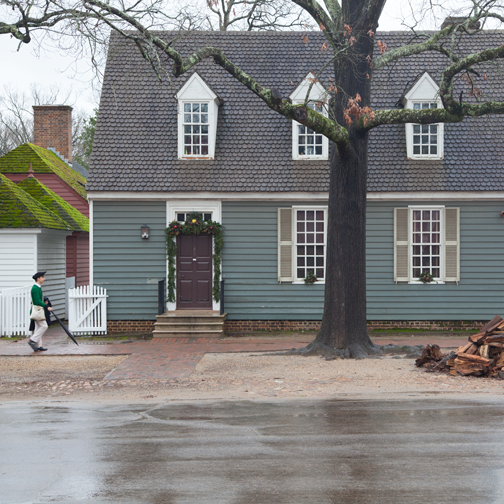 A man in period costume strolling the streets of Colonial Williamsburg, Virginia
