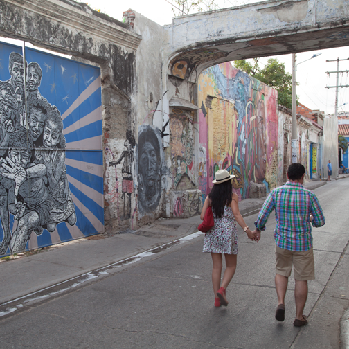 A couple walking past street art in Getsemani: Cartagena, Colombia