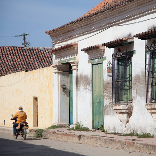 Weathered Colonial architecture and motorcyclist in Mompos: Mompox, Colombia
