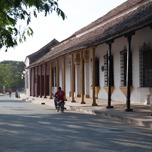 Motorcyclist riding near Colonial architecture in Mompos: Mompox, Colombia